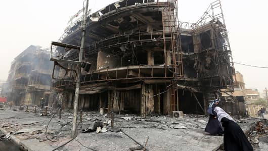 Iraqi women walk past a damaged building at the site of a suicide bombing in Baghdad's central Karrada district.