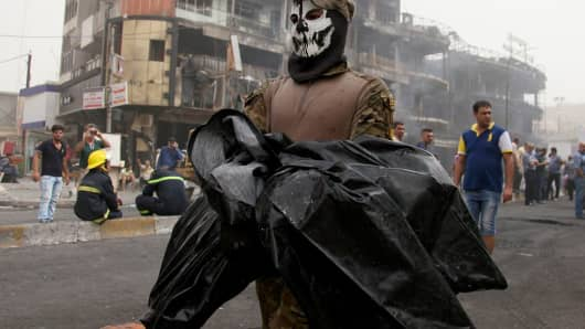 An Iraqi security officer carries the body of a victim of the bombing, which occurred as citizens broke their Ramadan fasts with dinner and shopping.