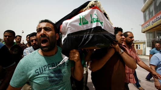 Men carry a coffin in the holy Iraqi city of Najaf during a funeral procession for the victims of the suicide bombing.