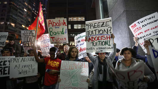 Students hold placards as they stage a demonstration at the Hunter College, which is a part of New York City University, to protest ballooning student loan debt for higher education and rally for tuition-free public colleges in New York on November 13, 2015.