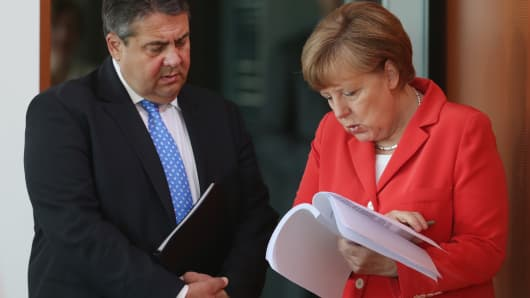 German Chancellor Angela Merkel and Vice Chancellor and Economy and Energy Minister Sigmar Gabriel look at an unidentified document prior to the weekly government cabinet meeting on May 13, 2015