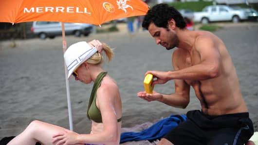 Sunbathers apply UV filter cream on their bodies.