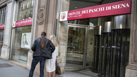Pedestrians walk outside a Banca Monte dei Paschi di Siena SpA bank branch in Milan, Italy.