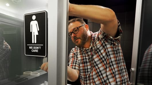 Museum manager Jeff Bell adheres informative backing to gender-neutral signs in the 21C Museum Hotel public restrooms on May 10, 2016, in Durham, North Carolina.