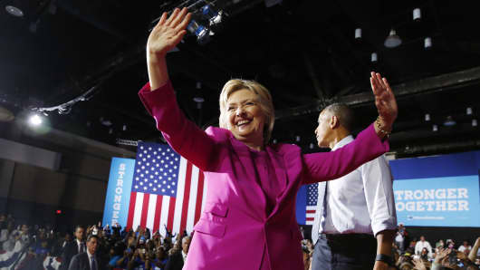 Democratic U.S. presidential candidate Hillary Clinton acknowledges supporters during a campaign rally, where she received the endorsement of U.S. President Barack Obama (R), in Charlotte, North Carolina, U.S., July 5, 2016.