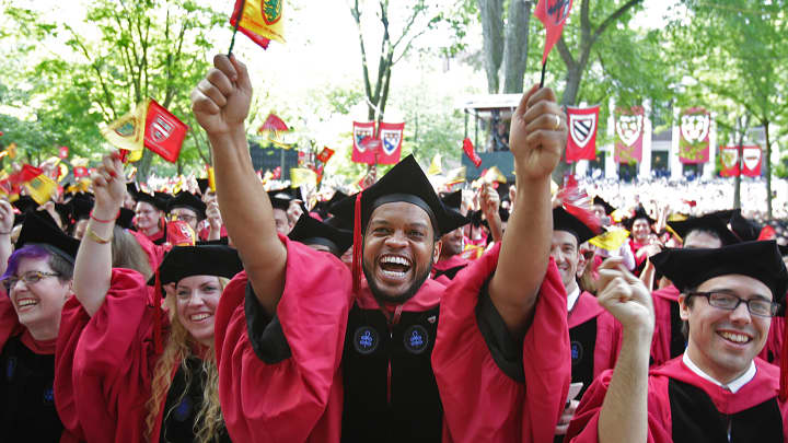 Students react as they prepare to receive their diplomas at commencement at Harvard University in Cambridge, Mass., on May 26, 2016.