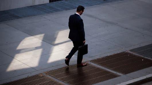 A pedestrian walks along Broad Street in New York.