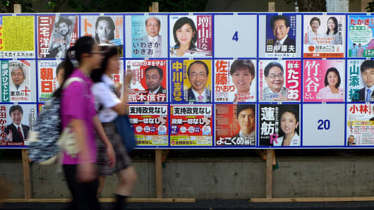 Schoolgirls walk in front of the July 10 upper house election campaign posters in Tokyo on July 7, 2016. The July 10 upper house election is the first nation-wide election after Japanese law changes its voting age from 20 years old to 18 years old in July 2016.