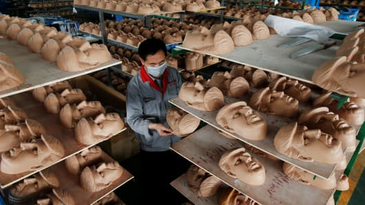 A worker checks a mask of U.S. Republican presidential candidate Donald Trump at Jinhua Partytime Latex Art and Crafts Factory in Jinhua, Zhejiang Province, May 2016.