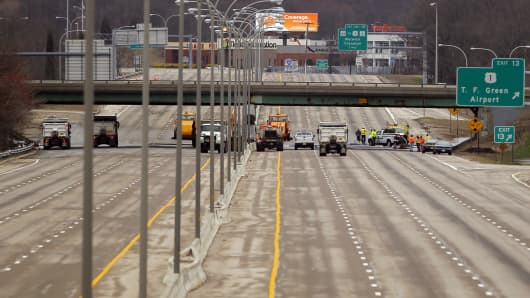 Crews work to clear the floodwaters causing the closure of Interstate 95 in Warwick, Rhode Island.