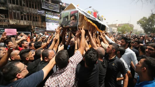 Mourners carry the coffin of an Iraqi man, who was killed in a suicide bombing that ripped through Baghdad's busy shopping district of Karrada earlier this week on July 3, 2016.