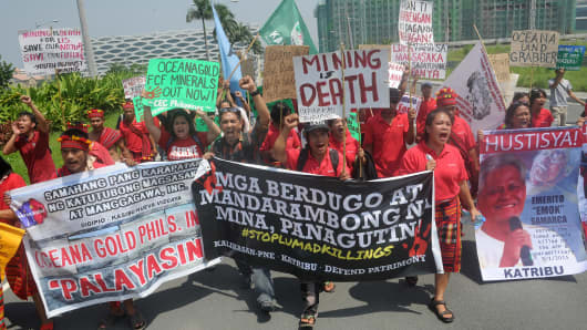 Environmentalists hold placards during a march to protest against the effects of mining, such as environmental degradation and lack of transparency, in Manila on September 15, 2015.