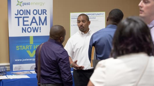 A Just Energy Group Inc. representative speaks with job seekers during the Best Hire Career Fair in Houston, Texas, U.S., on Thursday, July 7, 2016.