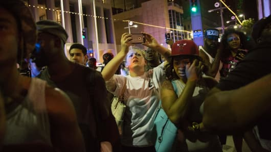 Protestors yell after police officers arrest a bystander following the shooting at a protest in Dallas on July 7, 2016.