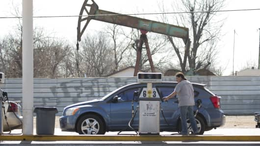 A motorist fills her car with gas at a gas station near an oil field pumping rig in Oklahoma City, Oklahoma.