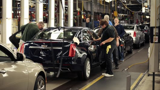 Employees work on a Cadillac CTS on the production line at the General Motors' Lansing Grand River Assembly plant in Michigan.