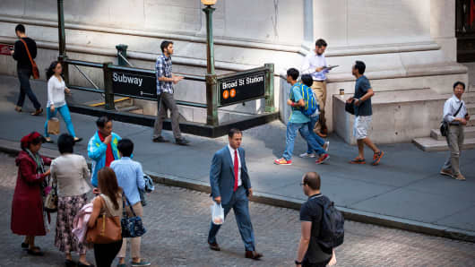 Pedestrians walk on Wall Street, near the New York Stock Exchange in June.