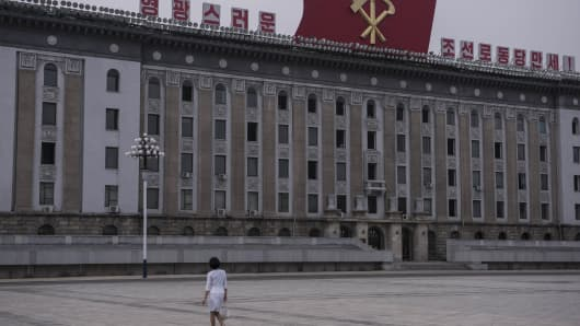 A woman walks across Kim Il-Sung square in central Pyongyang on July 7, 2016.