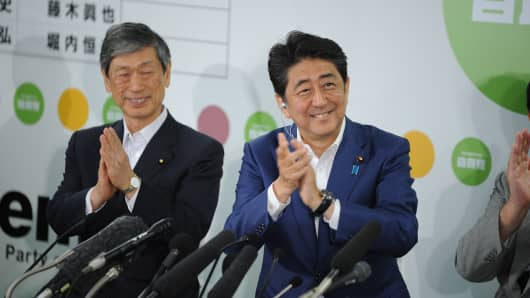Japanese Prime Minister Shinzo Abe (C) close to Vice President of LDP, Komura Mashiko (L) during a joint press conference during the 2016 Upper House Election on July 10, 2016, in Tokyo.