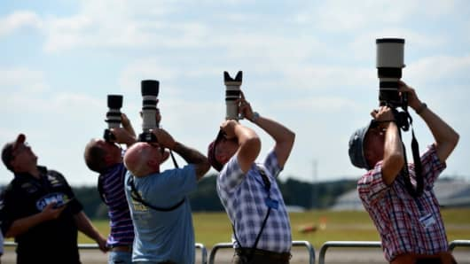 Airplane enthusiasts photograph an air display on the second day of the Farnborough International Air show in Hampshire.