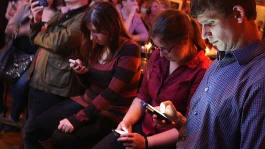 Young adults split their time between the televisied debate and Twitter on their smart phones during a debate watch party at the Local 16 bar and restaurant October 13, 2015 in Washington, DC.