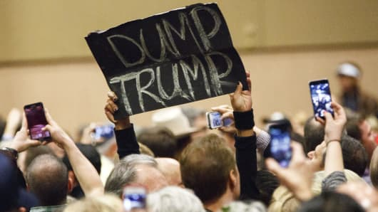 A protester's sign reads 'Dump Trump' during a campaign rally for Donald Trump, president and chief executive officer of Trump Organization Inc.
