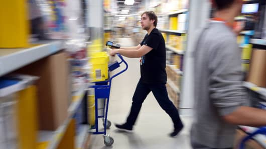 An employee pushes a trolley along an aisle at an Amazon.com fulfillment center.