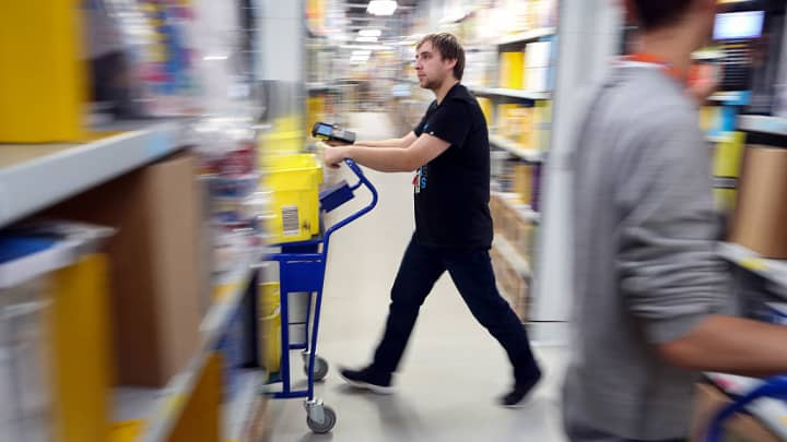 An employee pushes a trolley along an aisle at an Amazon.com fulfillment center.
