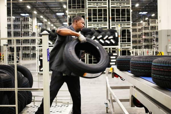A worker loads automotive tires onto a conveyor belt at the Continental Tire Sumter plant distribution warehouse in Sumter, South Carolina.
