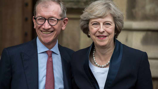 Britain's new Conservative Party leader Theresa May poses for a photograph with her husband Philip John May outside the Palace of Westminster in London on July 11, 2016.