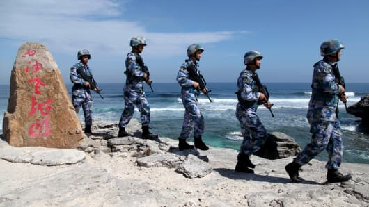 "Soldiers of China's People's Liberation Army (PLA) Navy patrol at Woody Island, in the Paracel Archipelago, which is known in China as the Xisha Islands, January 29, 2016. The words on the rock read, ""Xisha Old Dragon"". Old Dragon is the local name of a pile of rocks near Woody Island."
