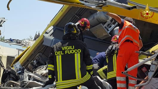 Firefighters work at the site where two passenger trains collided in the middle of an olive grove in the southern village of Corato, near Bari, Italy, in this handout picture released by Italian Firefighters July 12, 2016.