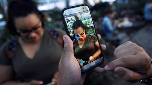 "A Pokemon appears on the screen next to a woman as a man plays the augmented reality mobile game ""Pokemon Go"" by Nintendo in New York City, July 11, 2016."