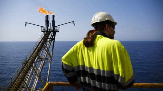 An oil worker looks on as flames burn from a gas venting pipe on the Casablanca oil platform, operated by Repsol SA, in the Mediterranean Sea off the coast of Tarragona, Spain.