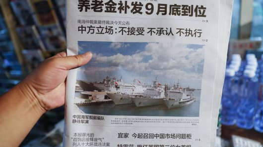 Headlines of the Beijing Evening newspaper of the Chinese naval fleet exercises displayed in a shop on July 12, 2016.