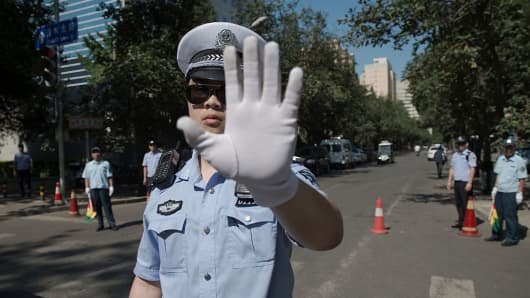 Chinese police officers block the road leading to the Philippines embassy in Beijing on July 13, 2016 the day after an international court on July 12 ruled against China in a Philippine challenge over Beijing-occupied territory in the South China Sea. Beijing on July 12 furiously rejected the ruling that rendered its claims in the South China Sea invalid and dealt a devastating diplomatic blow to its ambitions in the resource-rich region.