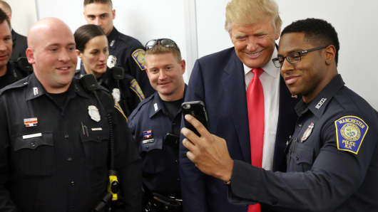 Republican presidential candidate Donald Trump takes a selfie with police officers