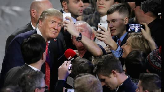 Republican presidential candidate Donald Trump poses for selfies with supporters