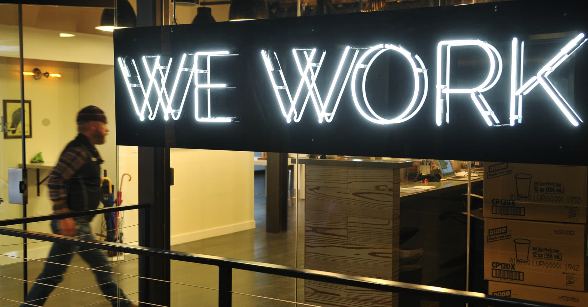 A man enter the doors of the 'WeWork' co-operative co-working space