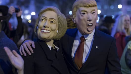 People wearing the masks of presidential candidates Hillary Clinton and Donald Trump