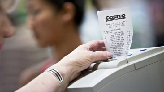A cashier waits for a receipt to finish printing at a Costco Wholesale store in Naperville, Illinois.