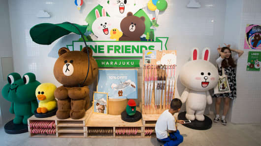A customer poses next to characters from the Line messaging app as a boy uses a smartphone inside Line Corp.'s LINE Friends Harajuku store on July 11, 2016 in Tokyo, Japan.