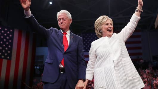 Democratic presidential candidate former Secretary of State Hillary Clinton (R) and her husband former U.S. president Bill Clinton greet supporters during a primary night event on June 7, 2016 in Brooklyn, New York.