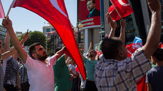 People wave Turkish flags during a march around Kizilay Square in reaction to the attempted military coup on July 16, 2016 in Ankara, Turkey.