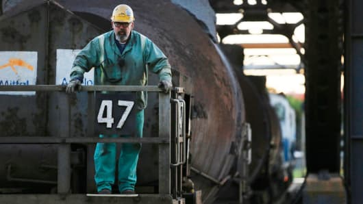 A worker stands on the rear platform of a bottle car full of molten steel inside the ArcelorMittal steel mill complex in Cleveland, Ohio.