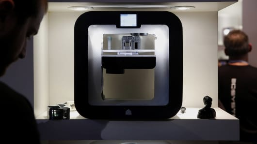 An attendee views the 3D Systems Inc. Cube printer during the 2014 Consumer Electronics Show (CES) in Las Vegas, Nevada.