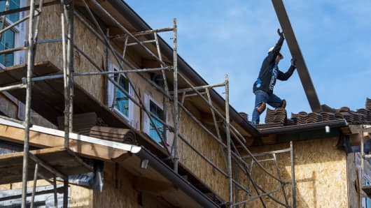 A contractor moves roofing material on a home under construction at the Toll Brothers Cantera at Gale Ranch housing development in San Ramon, Calif.