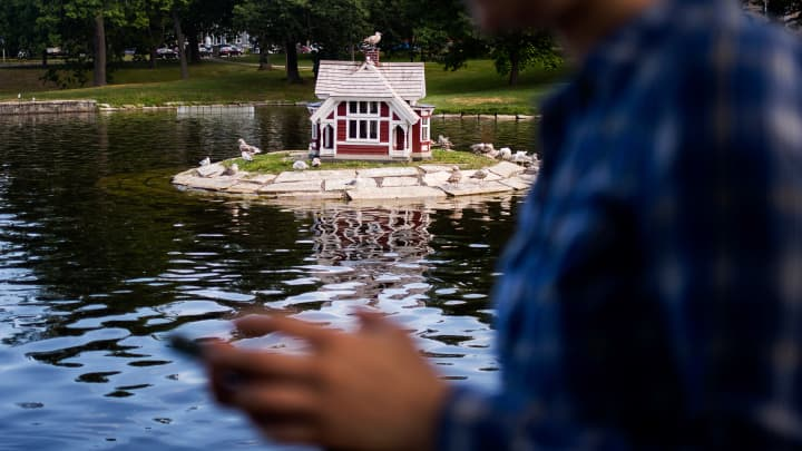 Anna Simmons, of Portland, gets as close as she can to the Victorian duck house in the middle of the pond at Deering Oaks Park while she plays Pokemon Go. The landmark, among other known Portland places, is a 'Poke Stop' in the game.