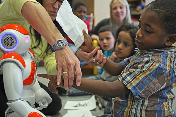 Tobi Adebayo, reaches out to the robot. The Moody School in Haverhill is one of just three places in the world using the NAO robot to work with students who have learning disabilities, including some with autism.