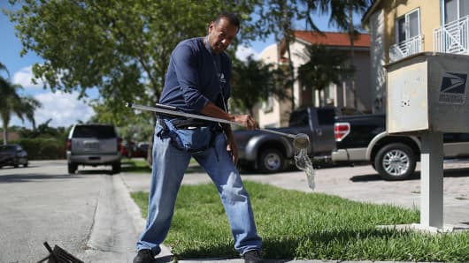Larry Smart, a Miami-Dade County mosquito control inspector, looks for signs of mosquito larva in a drainage ditch as he works on eradicating them as the county continues to be proactive in fighting a possible Zika virus outbreak on May 26, 2016 in Miami, Florida.